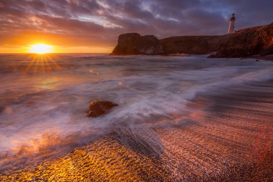 Sunstar by Christian Flores-Muñoz - Landscapes Waterscapes ( newport oregon, yaquina head, lighthouse, rocks, sunset, beach, oregon coast, clouds, sun, slow shutter )