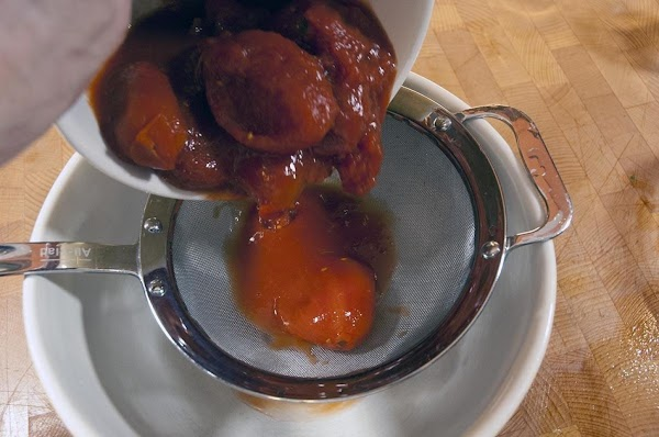 Use a strainer to separate the whole tomatoes from the juice.