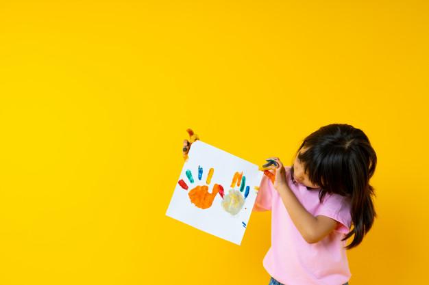 Imagem de uma menina segurando uma folha de sulfite na qual foram estampados com tinta guache suas mãos, com a finalidade de ilustrar as competências socioemocionais como potencializadoras do ensino. A menina está olhando para seu desenho.