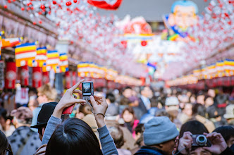 Photo: A woman takes pictures of the crowds at Asakusa's Hagoita Market