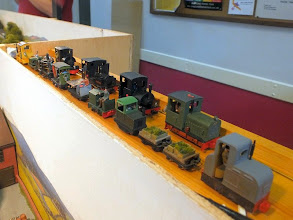 Photo: 018 A display of a small proportion of John Thorne's extensive locomotive roster on display above the Bottle Kiln Lane fiddle yard. The Minitrains Gmeinder diesel, a small proprietory HOe loco, at the head of the rear row of locos gives some scale to the tiny engines posed on the front row. Models featured are by Rusby's Resins, Nigel Lawton, RT Models, Saltford and scratchbuilt by John .