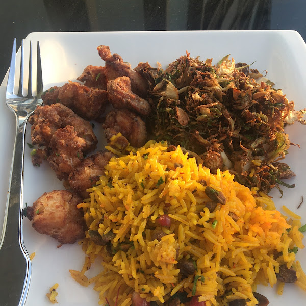 Fried chicken, saffron rice and Brussels sprout leaves plated at home