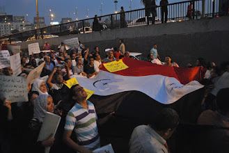 Photo: Journalists and others carry a large Egyptian flag bearing a cross and crescent, signifying an appeal to unity between all Egyptians regardless of religious belief.