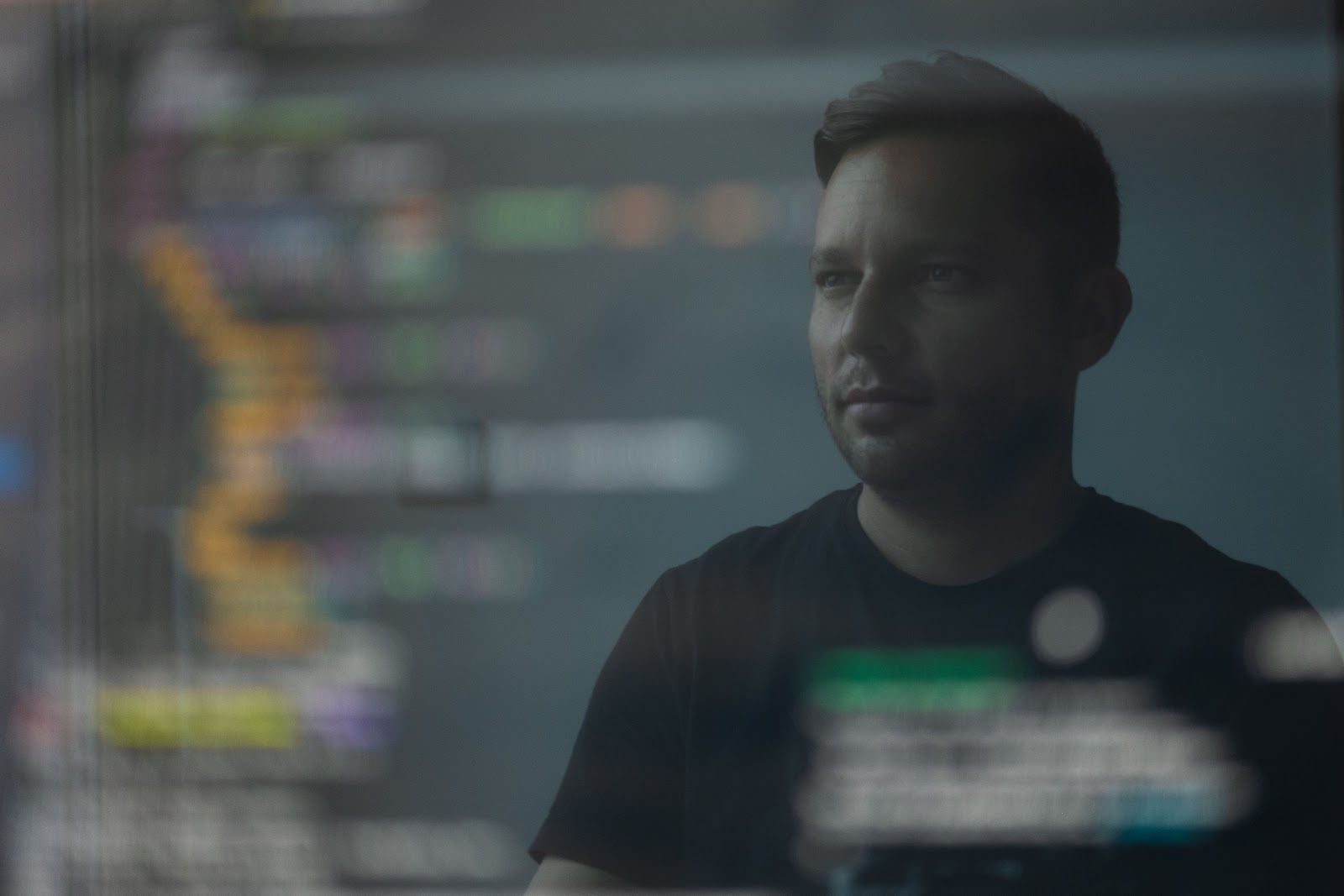a man in a black t-shirt looking at JavaScript code that is out of focus
