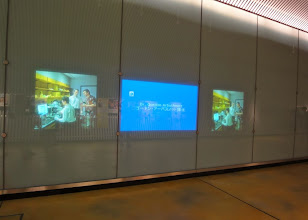 Photo: Hallway lined with monitors...