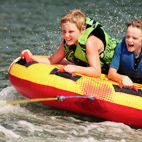 Trying to hold on to the tube by Amelia Rice - People Family ( water tubing, laughing, vacation, water sports, boys, summer, fun, rivers, people, smiling,  )