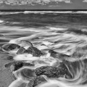 Hitting the rocks by Fariz Mohammad - Landscapes Beaches ( sands, monochrome, balck and white, wave, long exposure, beach, rocks, slow speed )