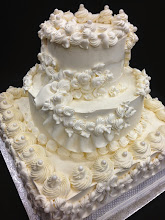 Photo: Ornate wedding cake (before glance) all in Ivory whipped cream frosting. This work of art features mini & large rosettes studded w/edible pearls, ribbon border around bottom, swoop ribbon border on middle tier, mini frosting roses w/foliage. Silver diamond wrap around bottom.