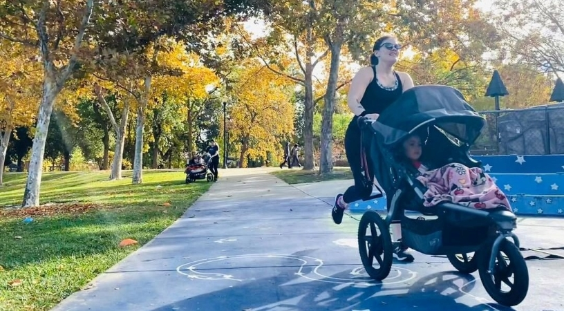 Woman pushing a baby jogger in a park in Brentwood, Los Angeles, CA