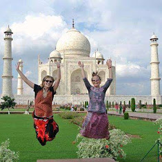 Two women taking a jumping shot photo with the Taj Mahal in India
