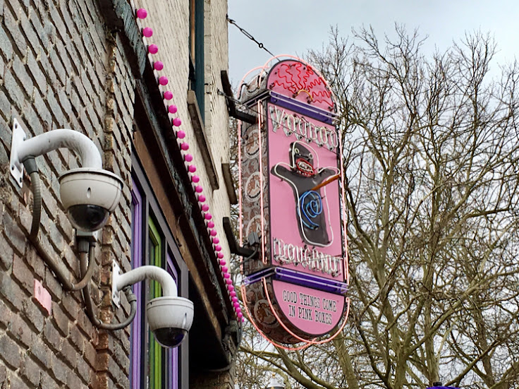 The pink sign depicts a voodoo doll - one of their most iconic donuts, filled with raspberry jelly, covered in chocolate frosting and stabbed with a pretzel stake.