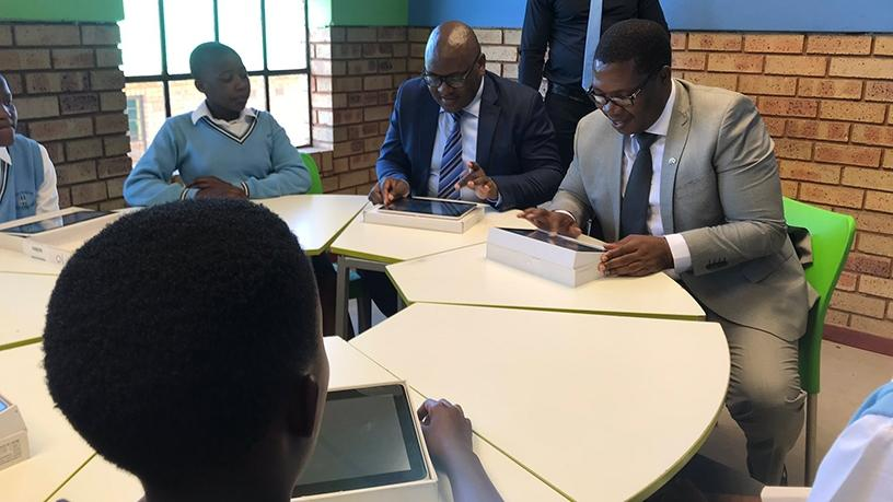 Premier David Makhura and MEC Panyaza Lesufi try out the smart devices that will be used by learners at Menzi Primary School. [Photo source: GDE Twitter page]