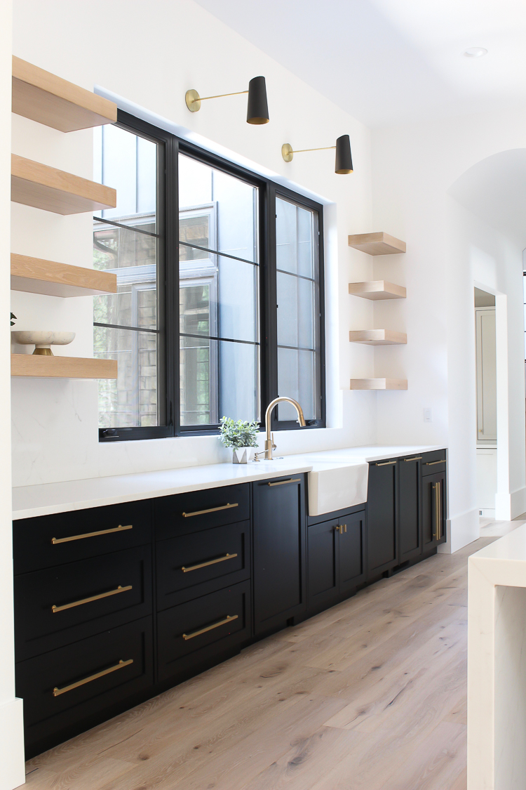 modern kitchen with black shaker cabinets, brass cabinet hardware, black and brass sconces and farmhouse sink