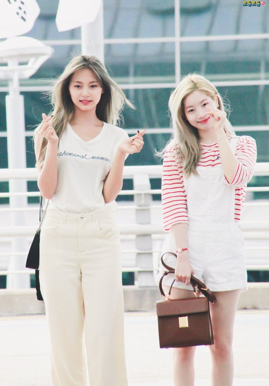 TWICE members Dahyun (left) and Tzuyu (right) showing hand hearts