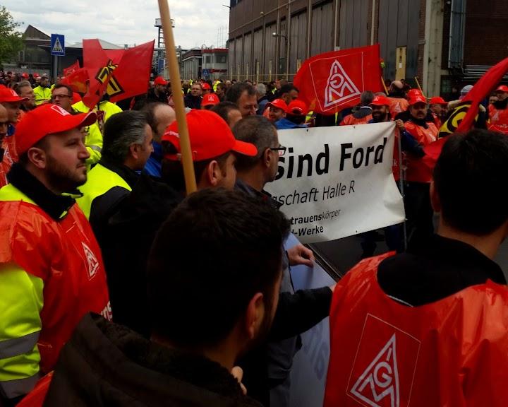 Streikende mit IG-Metall-Mützen, -Westen und -Fahnen. Transparent: «Wir sind Ford».