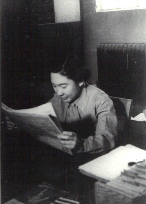 Dr. Tamie Tsuchiyama, then a grad student, reads a newspaper. She is seated and staring intently at the page.