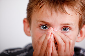 Photo: Boy about to sneeze covering his nose and mouth with his hands