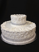 Photo: Floral piped wedding cake featuring design provided by bride. Silver diamond wrap around bottom of each tier.