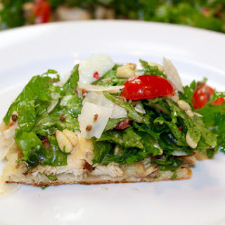 Chicken Artichoke Pizza Topped with Kale Tomato Pine Nut Salad