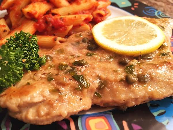 Veal With A Caper Sauce Along With Penne Pasta In The Background With Parsley And A Slice Of Lemon As A Garnish.