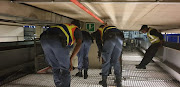 SAPS officers conducting a search between two baggage conveyor belts at OR Tambo International Airport during the festive season. A Hong Kong prison chaplain says several international airports are seeing an unprecedented rise in drug trafficking cases where product was moved from OR Tambo.