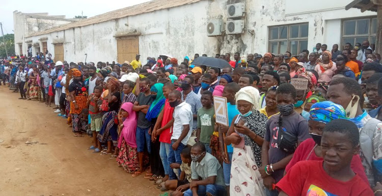 People wait for friends and relatives as a ship carrying more than 1,000 people fleeing an attack by Islamic State-linked insurgents on the town of Palma, docks in Pemba, Mozambique, on April 1 2021.