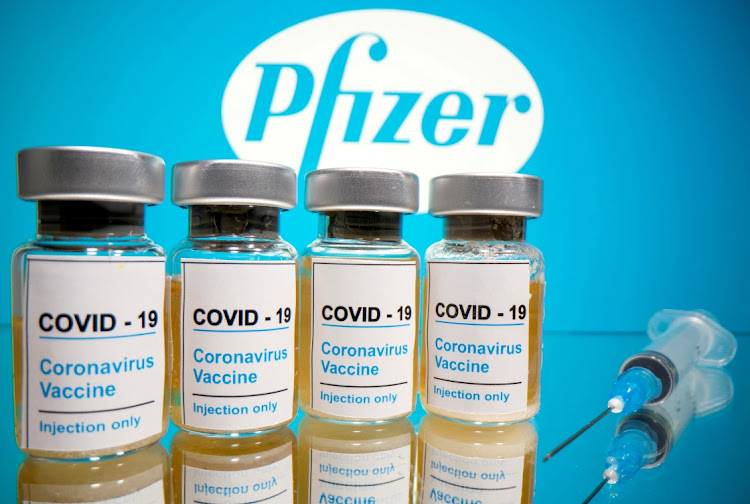 "Vials with a sticker reading, ""Covid-19 / Coronavirus vaccine / Injection only"" and a medical syringe are seen in front of a displayed Pfizer logo in this illustration."