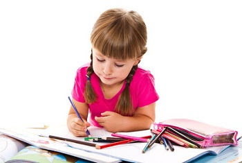 Little girl coloring with pencils in art book