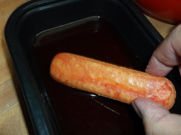 Place lady fingers, one at a time into strawberry juice; roll lady finger twice...