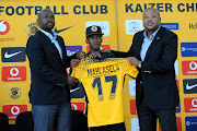 Kaizer Chiefs coach Steve Komphela, left, and team manager Bobby Motaung welcome new signee Kabelo Mahlasela, centre, during a media briefing at Chiefs Village in Johannesburg.