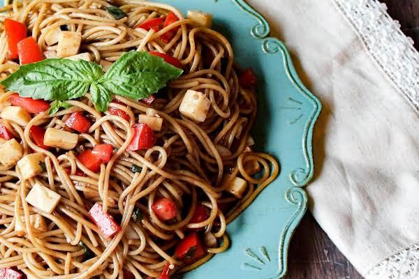 Spaghetti With Mozzarella And Tomato On A Blue Plate.
