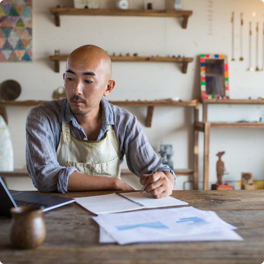 A man wearing a work apron sits at a table. His laptop is open and he's holding a pen, taking notes.