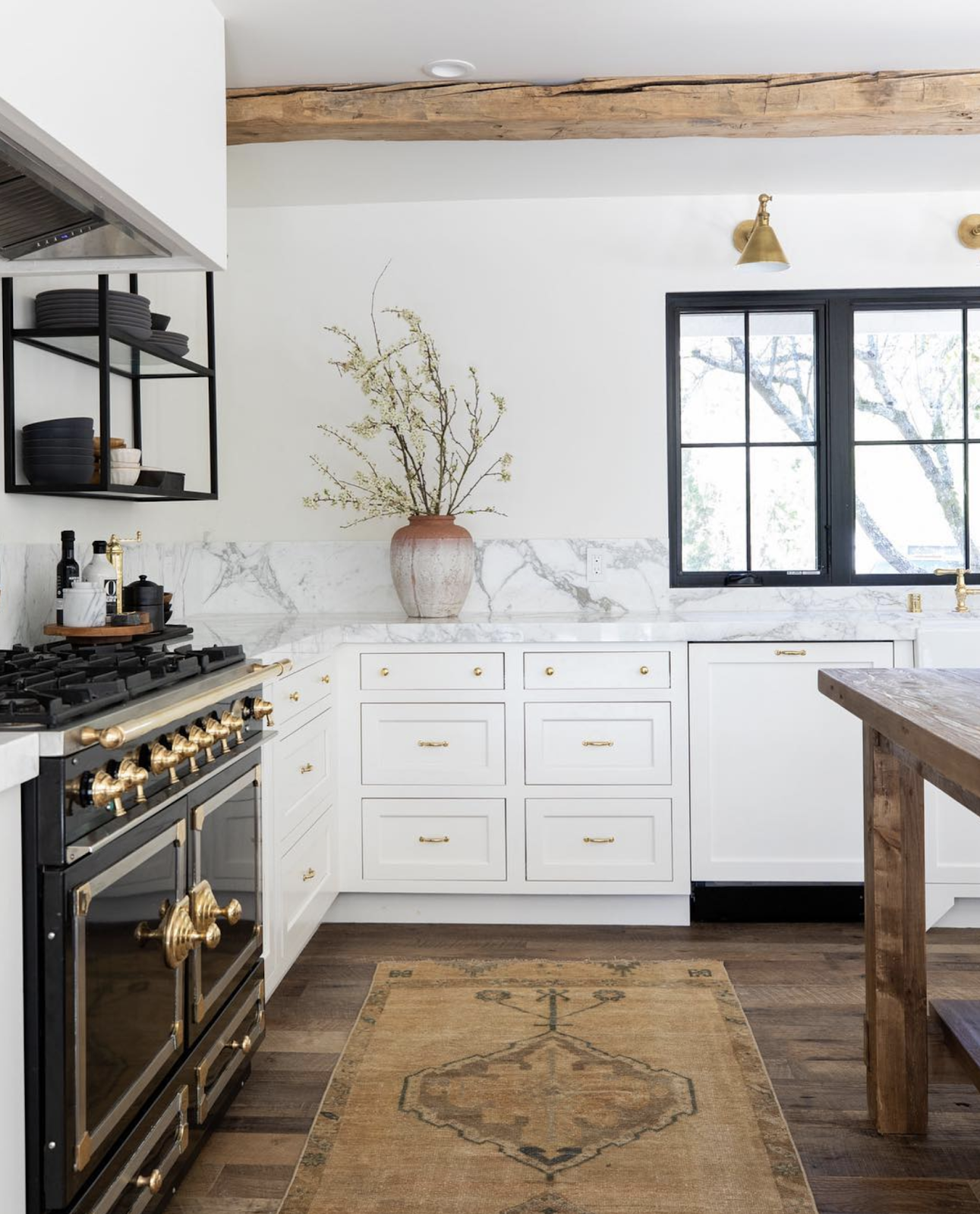 a unique white kitchen with black stove and white shaker cabinets. a wood beam spans the ceiling, matching a reclaimed wood center island. a marble countertop and backsplash ties in the color scheme of the space