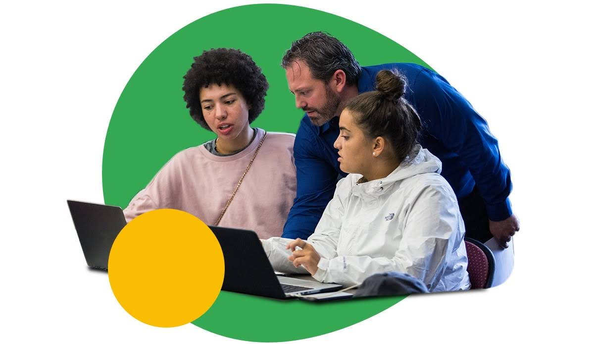 Professor teaching two students next to a laptop
