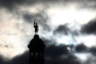 Photo: The sun burning through the clouds behind Captain Vancouver's statue atop the BC Provincial Legislature in Victoria BC Canada