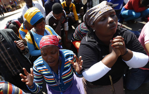 EMOTIONAL TIME: Supporters of arrested platinum mineworkers pray outside the Ga-Rankuwa Magistrate's Court in 2013. Picture: REUTERS