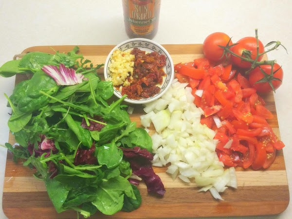 Dice up your tomatoes, onions, garlic, sun-dried tomatoes, chop up your greens if you...