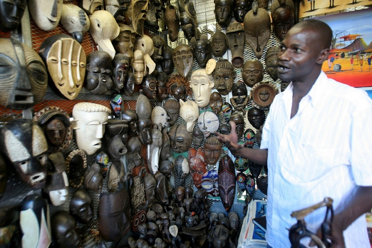 Issa Dialo of Senegal shows off his collection of masks at the African Crafts Market in Rosebank. Picture: Veli Nhlapo/Sowetan