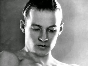 Photo: Male stars such as Rudolph Valentino were treated in a similar way, their hair and faces shiny and glowing.  Male stars, however, tended to be lit in these photographs in such a way as to emphasize the 3D modeling of the head.  In retrospect, this makes us realize how women's face were reduced to a flat surface: as if men act and move in space, whereas women become images to be gazed upon.