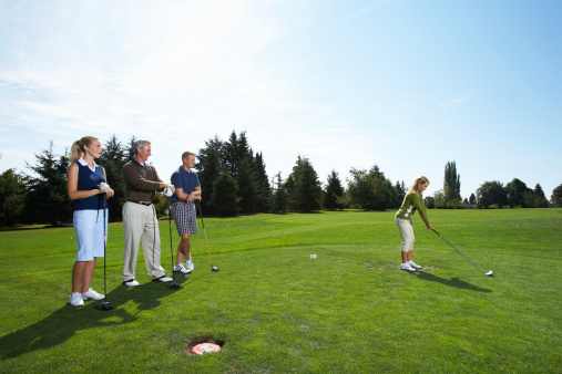 charity golf tournament players at a golf green golf course with blue sky.