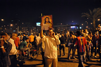 Photo: A Coptic Christian holds up a picture of Jesus Christ...
