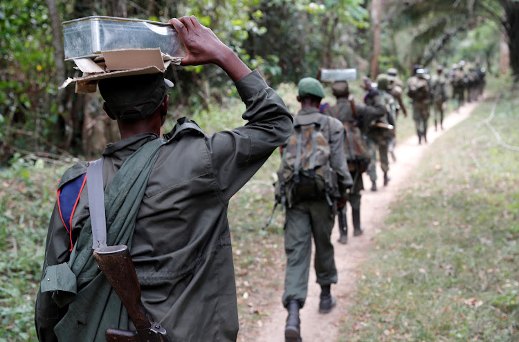 A Congolese soldier from the Armed Forces of the Democratic Republic of Congo carries a box with bullets on top of his head near town of Kimbau, North Kivu Province, DRC.