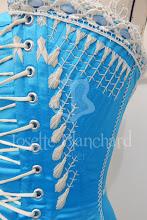 Photo: Ref.: CRM 1876 01 Valor: R$ 800,00 Corset Midbust réplica Vitoriana datado de 1876 em cetim bucol azul com fechamento frontal por busk com renda guipure passa-fitas no decote e flossing bege.  Confeccionado em cetim bucol na camada externa, duas camadas de sarja 100% algodão, uma camada de entretela e forro em tricoline 100% algodão. São a partir de 42 barbatanas espiraladas e 4 barbatanas flats em aço temperado revestido ou aço inóx ( o número de barbatanas varia de acordo com as medidas), mais busk em aço inóx. O busk facilita para vestir e retirar o corset além de dar sustentação à frente do corset. O valor padrão refere-se às medidas até 89 cm de cintura. Para peças com medidas maiores, entre em contato. Verifique disponibilidade de modelo, tecidos e cores entrando em contato. O tom pode variar dependendo da calibragem de cor do seu monitor ou celular.  Também disponível nos tecidos e cores: - Cetim rosa antigo; - Cetim roxo;  - Crepe vogue rosa claro; - Crepe vogue rosa; - Crepe vogue roxo; - Crepe vermelho; - Crepe preto; - Cetim azul.