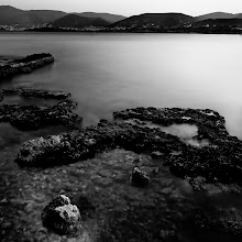 """Photo: a sea's gift   for #MonochromeMonday curated by +Siddharth Pandit  #MoodyMonday curated by +Philip Daly  & +Joel Tjintjelaar's #BWFineArtLE  A girl's adventures with long exposure  Have I ever told you what's the single thing I'd change about the place I live? No? NOT yet?!!! Well, I really don't know how that slipped me.  Well, it's simple. I'm talking about wind. No need to array here all the moments it can turn from perfect to most annoying, I suppose many of you already have quite a few examples. But to have the chance to be in the perfect place at the right moment, with some beautiful reddish rocks lying at your feet, the sea to embrace and make them shine happy, and a perfect sunset in the distance and not being able to get home with a SINGLE usable LE shot because the wind was so harsh that you had to hold your tripod still with your hands, after having loaded it with pounds and pounds in gravel to keep it there, to almost fall from said rocks trying to catch the cable release lid that flew away like a piece of paper (and not being able to save it, but only to rip off a boot in the process when you got your leg stuck in a rock's crack) ….and so on and so forth... well, that is the utmost """"luck"""" and the """"best"""" present wind can give you. How not truly deeply madly """"love""""wind after that?  OK, all is not bad because that was only on Sunday. Happily, I was out on Saturday too, chasing a couple of tiny clouds at Porto Rafti, near Athens, clouds that were so feeble (or playful maybe) that wouldn't even last for a 2 and a half minutes exposure, so I had to give up on them and concentrate on the sea, which at least was kind enough and gave me a few shots. And that's why I love sea all the way and never complain about it, she's so sweet to me every time:) One of the shots she gave me is this one.  Have a great ….... (fill in with whatever suits the case: evening/ morning/ night/ etc.) everyone!!!"""