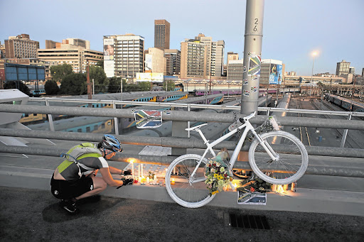 A cyclist lights a candle under a 'ghost bike' that was chained to the Nelson Mandela Bridge in Johannesburg on Friday night as a tribute to Olympic cyclist Burry Stander, who was killed this week