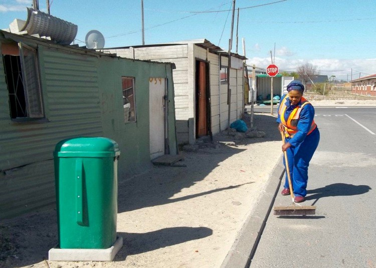 Zingiswa Tshwela sweeps the informal settlement. Since 2009, she has lived in a shack without access to a toilet. Some in Bholobholo have lived this way for even longer.