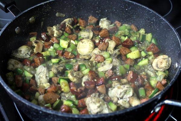 Add garlic, mushrooms, oysters with liquor (juice from can) and half of the sausage....