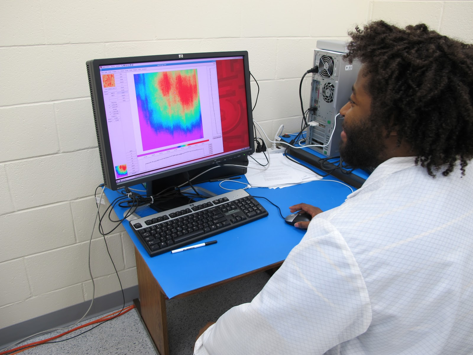 Dr. Mosby in his white lab coat sitting at a computer with a brightly colored plot on his computer.
