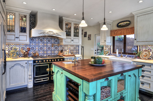 colorful spanish kitchen with painted tile backsplash and bright teal kitchen island with a butcher block countertop and small sink