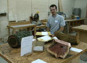 Photo: New member Michael Hanrahan at the Silent Auction table with walnut, eastern red cedar, mulberry, and osage orange, plus a gift certificate